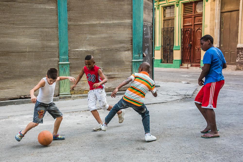 A group of boys play soccer on the street in Havana, Cuba