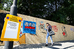 © Licensed to London News Pictures. 22/08/2019. London, UK. A woman walks past a residential property which has been boarded with parking suspended sign ahead of the 2019 Notting Hill Carnival in West London, which takes place this bank holiday weekend. Up to 1 million people are expected to attend the biggest street party in Europe. Photo credit: Dinendra Haria/LNP