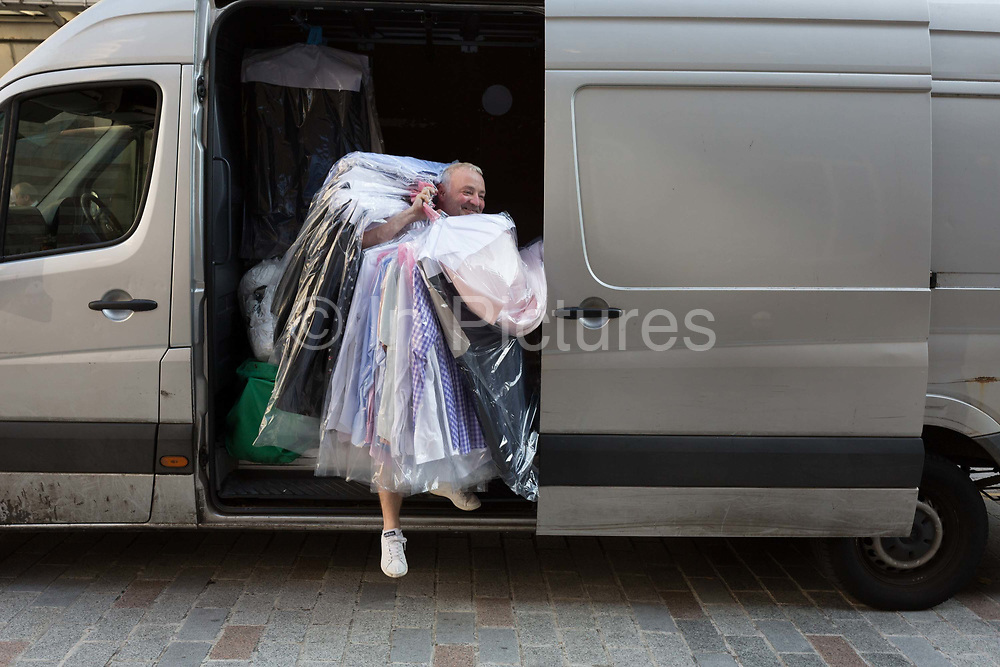 Emerging from his van, a dry cleaning contractor gathers many items of freshly-cleaned business clothing and delivers to a nearby address in the City of London - the capitals financial district, on 10th October 2018, in London, England.