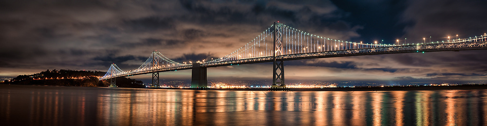 The Bay Lights shimmer on the cables of the San Francisco Bay Bridge as the moon shines overhead a partly cloudy night sky. San Francisco, CA.