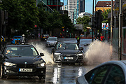 London, United Kingdom, July 28, 2021: Public and private transport vehicles are seen splashing through the flooded roads near Nine Elms in South West London on Wednesday, July 28, 2021. After torrential rain on Sunday caused widespread floods in different parts of Britain's capital city as drains were overwhelmed, downpours are seen across the capital prompting fears of further flooding in London this Wednesday. (VX Photo/ Vudi Xhymshiti)
