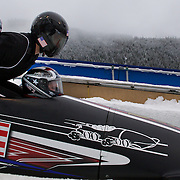 "The USA team-1 load into the bobsleigh during the Bobsleigh Four-man competition  at The Whistler Sliding Centre, Whistler, during the Vancouver Winter Olympics. 25th February 2010. Photo Tim Clayton..'BOB'..Images from the Four-man Bobsleigh Competition. Winter Olympics, Vancouver 2010..History was made at the Whistler Sliding Centre when the USA four-man bobsleigh team, led by Steven Holcomb took the Gold. The first time since 1948, a gap of 62 years, since the USA have won an Olympic Bobsleigh gold and they did it with their sleigh named ""Night Train""...The four days of practice and competition show the tension, nervousness and preparation as the teams of hardened men cope with the challenge of traveling at average speeds of over 150 km an hour. Indeed, five teams had already pulled out of the event before the opening heats because of track complexity, speed and fear, and on the final day, another four teams did not start after six crashes in the first two heats...Teams warm up behind the start complex, warming muscles in the cold in preparation for the explosive start. Many teams prepare in silence, mentally preparing themselves as they wait at the top of the run, in the bobsleigh sheds and the loading areas for their turn. When it's time to slide each team performs it's own starting ritual, followed by the much practiced start out of the blocks for just over four seconds, the teams are then in the hands of the accomplished drivers as they hurtle down the track for just over fifty seconds...Spectators clamber for the best position on track to see the sleighs for a split second, many unsuccessfully try to capture the moments on camera, The rumble of the sleigh is heard then the crowds gasp as it hurtles past in a blur...The American foursome of  Steven Holcomb, Justin Olsen, Steve Mesler and Curtis Tomasevicz finished with a pooled four-heat time of 3min 24.46sec. The German team led by Andre Lange won the Silver Medal in a combined time of 3min 24.84sec while th"
