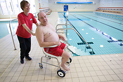 Disabled man leaving the swimming pool at his local leisure centre with the assistance of a member of staff,