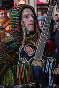 A man with long dreadlocks plays an acoustic guitar during a Hare Krishna street dance on New Years Eve at Piccadilly on the 31st December 2019 in London in the United Kingdom.