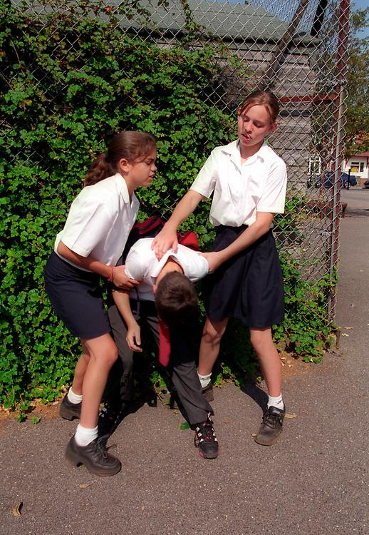 Girls bullying smaller boy at school modelled,