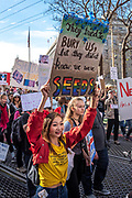 """San Francisco, USA. 19th January, 2019. The Women's March San Francisco proceeds down Market Street. A young woman smiles as she holds a sign reading: """"They tried to bury us, but they didn't know we were seeds."""" Credit: Shelly Rivoli/Alamy Live News"""