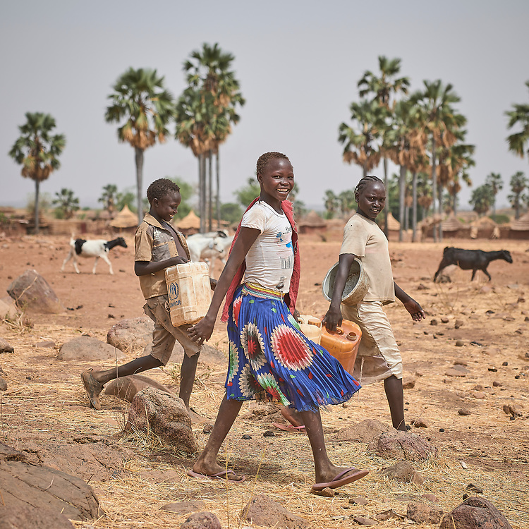 Children walk to fetch water in Lugi, a village in the Nuba Mountains of Sudan. The area is controlled by the Sudan People's Liberation Movement-North, and frequently attacked by the military of Sudan. Hundreds of wells have been drilled in the Nuba Mountains by the Catholic Church, which also sponsors schools and health care facilities throughout the war-torn region.