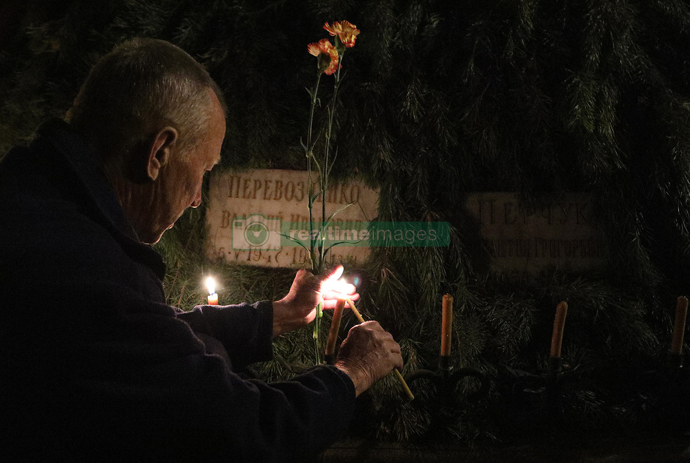 April 25, 2018 - Kyiv, Ukraine - A man lights a candle at the To the Heroes of Chormobyl memorial kurgan during a commemorative prayer service for the victims of the Chornobyl accident 32 years after the tragedy, Kyiv, capital of Ukraine, April 25, 2018. Ukrinform...KYIV. People have gathered at the To the Heroes of Chornobyl memorial kurgan at midnight to pay tribute to those who died as a result of the Chornobyl (Chernobyl) disaster. The accident at the fourth reactor of the Chornobyl Nuclear Power Plant took place 32 years ago at night on April 26, 1986. (Credit Image: © Danil Shamkin/Ukrinform via ZUMA Wire)