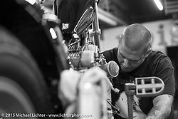 Adam Munz helping with final prep on Brandon Casquilho's motor at Noise Cycles the night before Born Free 6. Santa Ana, CA. USA. June 26, 2014.  Photography ©2014 Michael Lichter.