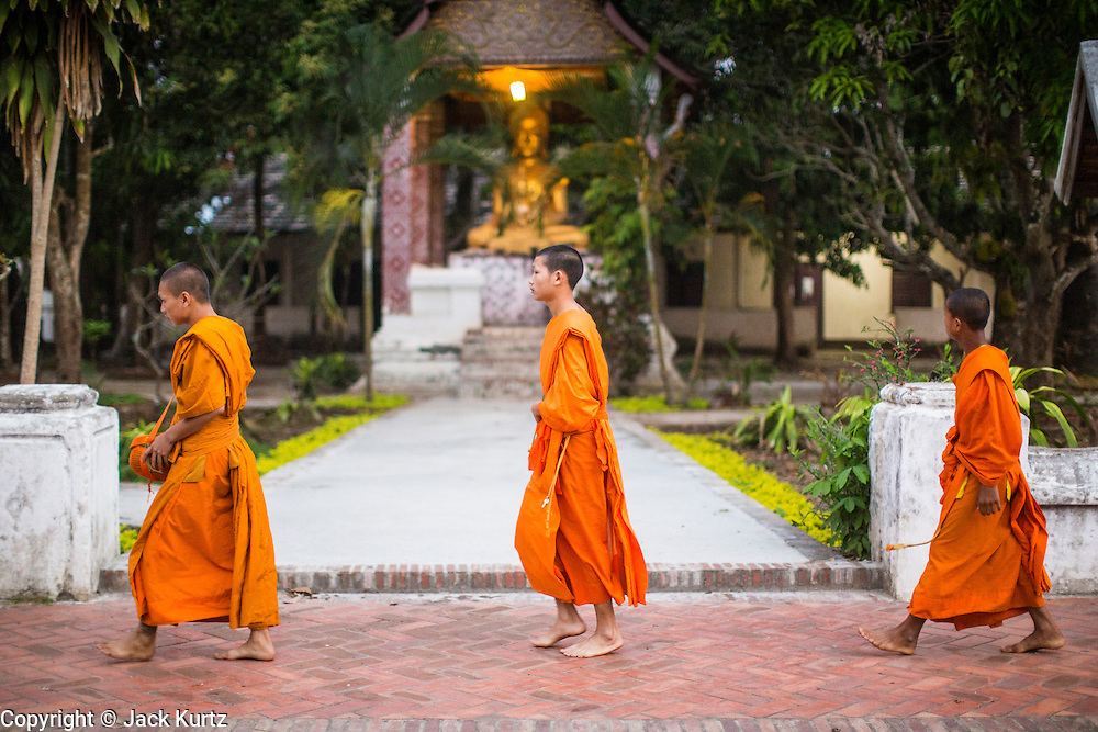 """11 MARCH 2013 - LUANG PRABANG, LAOS:  Buddhist monks walk past a statue of the Buddha in a temple in Luang Prabang during the tak bat. The """"Tak Bat"""" is a daily ritual in most of Laos (and other Theravada Buddhist countries like Thailand and Cambodia). Monks leave their temples at dawn and walk silently through the streets and people put rice and other foodstuffs into their alms bowls. Luang Prabang, in northern Laos, is particularly well known for the morning """"tak bat"""" because of the large number temples and monks in the city. Most mornings hundreds of monks go out to collect alms from people.   PHOTO BY JACK KURTZ"""