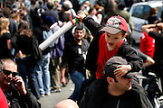 Le Coup De Grace - child with sword and father, anarchist parade, May Day March, Paris, 1 May 2009. Child apparently attempting to behead his father, not realising that if his father has no head, he will have nothing to hold on to!