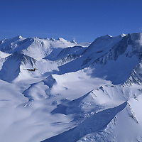 A Twin Otter ski plane flies by the 16,067' Mount Massif, Antarctica's highest mountain.
