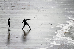 Two people seen in silhouette and from a distance on Fistral Beach in Newquay, Cornwall.