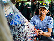 23 AUGUST 2018 - TELUK KUMBAR, PENANG, MALAYSIA: A fisherman repairs his nets in Teluk Kumbar on the island of Penang. Fishermen on Penang, an island off the west coast of mainland Malaysia, are being pressured by the island's resort development and reduce catches in the waters off Malaysia.     PHOTO BY JACK KURTZ
