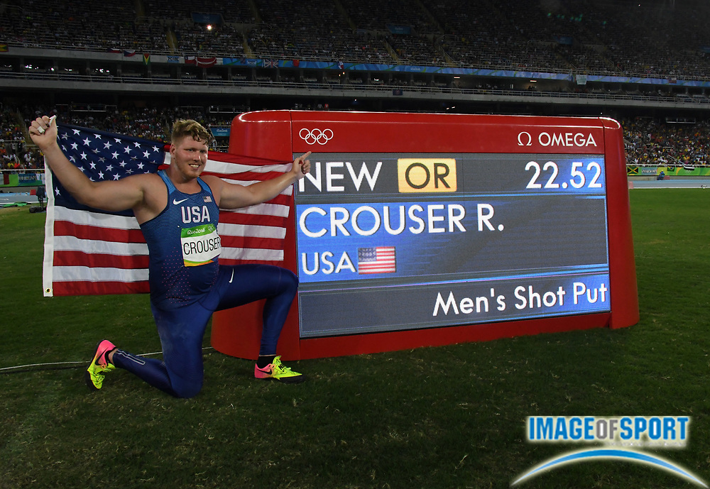 Aug 18, 2016; Rio de Janeiro, Brazil; Ryan Crouser (USA) poses with United States flag and scoreboard after winning the shot put in an Olympic record 73-10¾ (22.52m) during the 2016 Rio Olympics at Estadio Olimpico Joao Havelange.