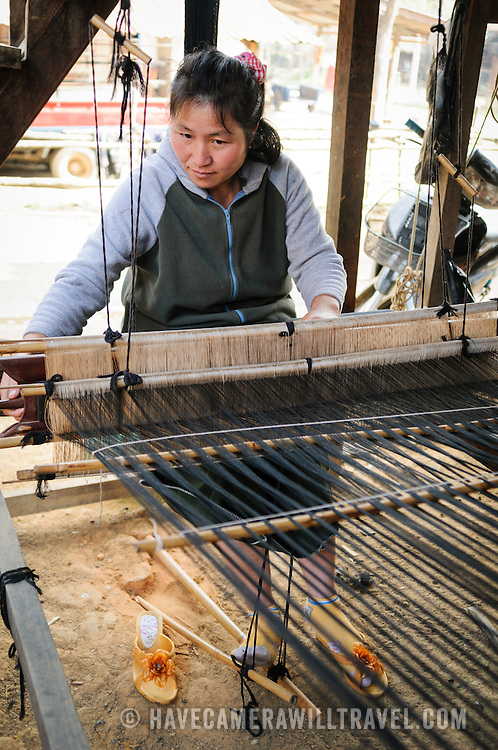 A woman uses her loom in weaving silk fabric in northeastern Laos. The loom is set up under her house, on the dirt floor.