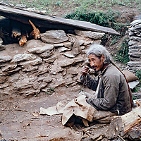 A Sherpa elder repairs a leather pack bag In the Khumbu region of Nepal.