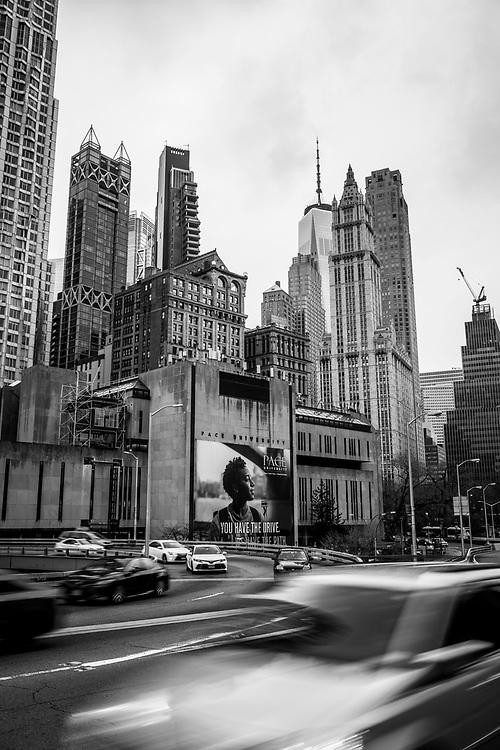 New York City, USA - March 19, 2020: Vehicles depart Lower Manhattan via the Brooklyn Bridge.