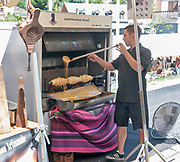 Cooking a cake on a spit over a wood fire, Sunday Market at Arreau, Hautes-Pyrénées, France.