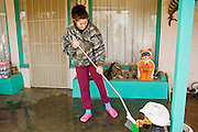 24 JANUARY 2010 -- WENDEN, AZ: Bridgett Edwards (CQ) cleans her grandparents porch in front of their home in Wenden Saturday.  Wenden was slammed by its second 100 year flood in 10 years on Thursday night when water raced through Centennial Wash and into the small town in La Paz County west of Phoenix. Most of the town's residents were evacuated to Red Cross shelters in Salome, about 5 miles west of Wenden.    PHOTO BY JACK KURTZ