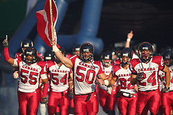 16.07.2011, Ernst Happel Stadion, Wien, AUT, American Football WM 2011, United States of America (USA) vs Canada (CAN), im Bild team canada enters the field, Steve Faoro (Canada, #50, LB) with the canadian flag in front // during the American Football World Championship 2011 game, USA vs Canada, at Ernst Happel Stadion, Wien, 2011-07-16, EXPA Pictures © 2011, PhotoCredit: EXPA/ T. Haumer