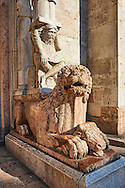 Lions with Atlas on their back holding up a column that supports the canopy above the main portal of the 12th century Romanesque Ferrara Duomo, Italy . Ferrara Cathedral (Basilica Cattedrale di San Giorgio, Duomo di Ferrara) is a Roman Catholic cathedral and minor basilica in Ferrara, Northern Italy. The original Romanesque design of Ferrara Cathedral is manifest in the façade. In the centre of the façade of Ferrara Cathedral is a porch, supported by two columns with Atlases seated on lions at the bases. It is decorated with a Last Judgement by an unknown master and a loggia with a Madonna and Child (a late Gothic addition). The portal of Ferrara Cathedral is the work of the sculptor Nicholaus, a pupil of Wiligelmus. The lunette shows Saint George, patron saint of Ferrara, slaying the dragon; scenes from the Life of Christ appear on the lintel. The jambs framing the entrance of Ferrara Cathedral are embellished with figures depicting the Annunciation and the four prophets who foretold the coming of Christ.<br /> <br /> Visit our ITALY PHOTO COLLECTION for more   photos of Italy to download or buy as prints https://funkystock.photoshelter.com/gallery-collection/2b-Pictures-Images-of-Italy-Photos-of-Italian-Historic-Landmark-Sites/C0000qxA2zGFjd_k<br /> <br /> If you prefer to buy from our ALAMY PHOTO LIBRARY  Collection visit : https://www.alamy.com/portfolio/paul-williams-funkystock/ferrara.html .