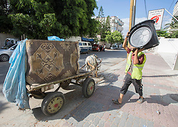 © Licensed to London News Pictures. 17/07/2014. Gaza.   On the tenth day of the war between Hamas and Israel a 5 hour cease fire is agreed.  A local rubbish collector takes the chance to empty the bins in Gaza city.    Photo credit : Alison Baskerville/LNP