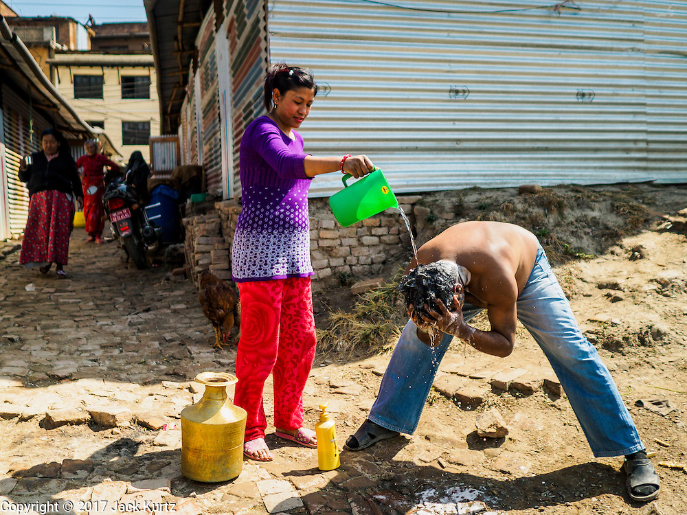 03 MARCH 2017 - BHAKTAPUR, NEPAL: A man washes up in front of his temporary shelter in an informal IDP center in Bhaktapur. He's been living in the temporary shelter with his family for nearly two years. Bhaktapur, a popular tourist destination and one of the most historic cities in Nepal was one of the hardest hit cities in the earthquake. Recovery seems to have barely begun nearly two years after the earthquake of 25 April 2015 that devastated Nepal. In some villages in the Kathmandu valley workers are working by hand to remove ruble and dig out destroyed buildings. About 9,000 people were killed and another 22,000 injured by the earthquake. The epicenter of the earthquake was east of the Gorka district.      PHOTO BY JACK KURTZ