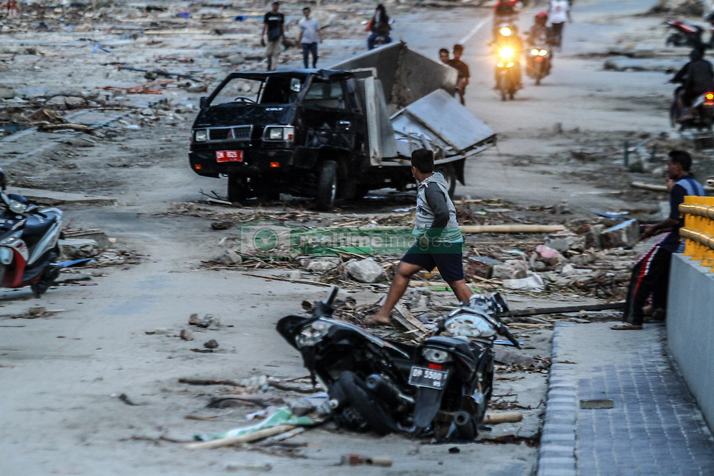 October 2, 2018 - Palu, Central Sulawesi, Indonesia - Indonesian people see a car that is destroyed in Palu on October 2, 2018, after magnitude 7.5 earthquake and tsunami hit the area on September 28. The Indonesian government on October 2 said the death toll from a devastating quake-tsunami on the island of Sulawesi had risen to 1,234 people, up from the previous count of 844 have been confirmed dead slammed into Indonesia's coastline on the island of Sulawesi, causing thousands of homes to collapse, along with hospitals, hotels and shopping centers. Emergency services fear that the death toll could rise into the thousands as rescue teams made contact with the nearby cities of Donggala and Mamuju and strong aftershocks continue to rock the city. (Credit Image: © Ivan Damanik/ZUMA Wire)
