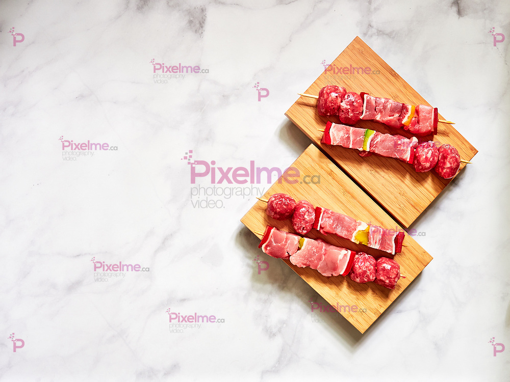 uncooked beef skewers top down view isolated over a wood plank with a clear white background in studio