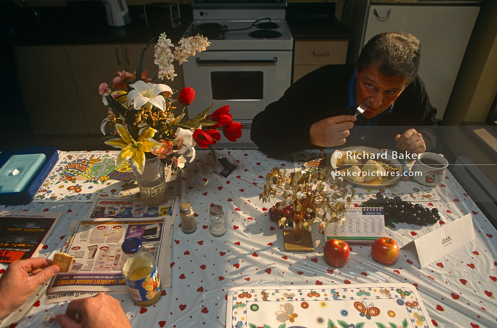 With fresh flowers and fruit on the table, a local authority worker tucks in to breakfast at his depot canteen, on 11th January 1999, in Quebec City, Quebec, Canada.
