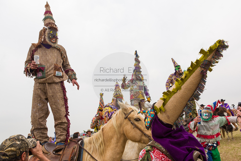 Costumed revelers stand on horseback during the traditional Cajun Courir de Mardi Gras chicken run February 15, 2015 in Church Point, Louisiana. The event involves 900-hundred costumed revelers competing to catch a live chickens as they move from house to house throughout the rural community.