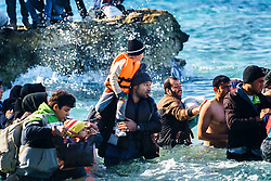 Nov. 9, 2015 - Cesme, Turkey - A man try to get on boat with son. Migrants travel by dinghy to the Greek island of Chios, from Turkish coast near Cesme, Izmir, Turkey, Thursday, Nov. 5, 2015. More than 300,000 people have traveled on dinghies and boats from nearby Turkey to Greek islands this year, with dozens dying along the way. (Credit Image: © Halit Onur Sandal/NurPhoto via ZUMA Press)