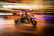 A tuk tuk blazes past during rush hour on a busy Bangkok night.