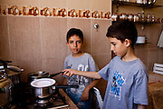 Anass preparing their own meal for lunch helped by his twin brother, while their parents are out.