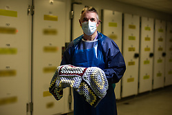 """© Licensed to London News Pictures . 19/02/2021. Salford , UK . NAME TAGS ON MORTUARY FRIDGES BLURED AT SOURCE . Pictured in the Salford Royal Hospital Mortuary , Mortuary Operations Manager MIKE COOMBES (55) holds a knitted blanket , donated by a member of the public in response to the hospital's """"Swan"""" appeal for end of life comforts and keepsakes for patients and their loved ones . A look at the end of life care provided at Salford Royal Hospital during Coronavirus restrictions . Photo credit : Joel Goodman/LNP"""