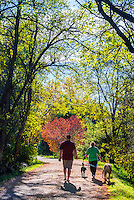 Couple walking their dogs on the Highline Canal path on an Autumn afternoon, Littleton, Colorado USA.