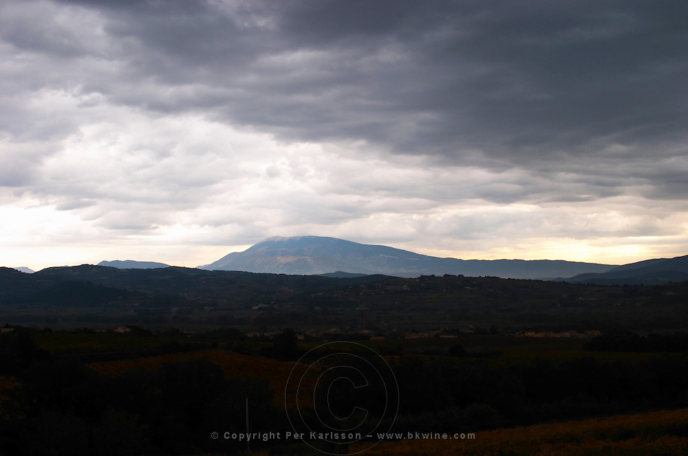 The Mont Ventoux from the north from a distance the top covered in snow. in mist, valley with villages in front, vineyards, storm clouds, evening silhouette.  Vaucluse, France, Europe