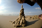 Hand dripping wet sand onto a sand castle on the beach.