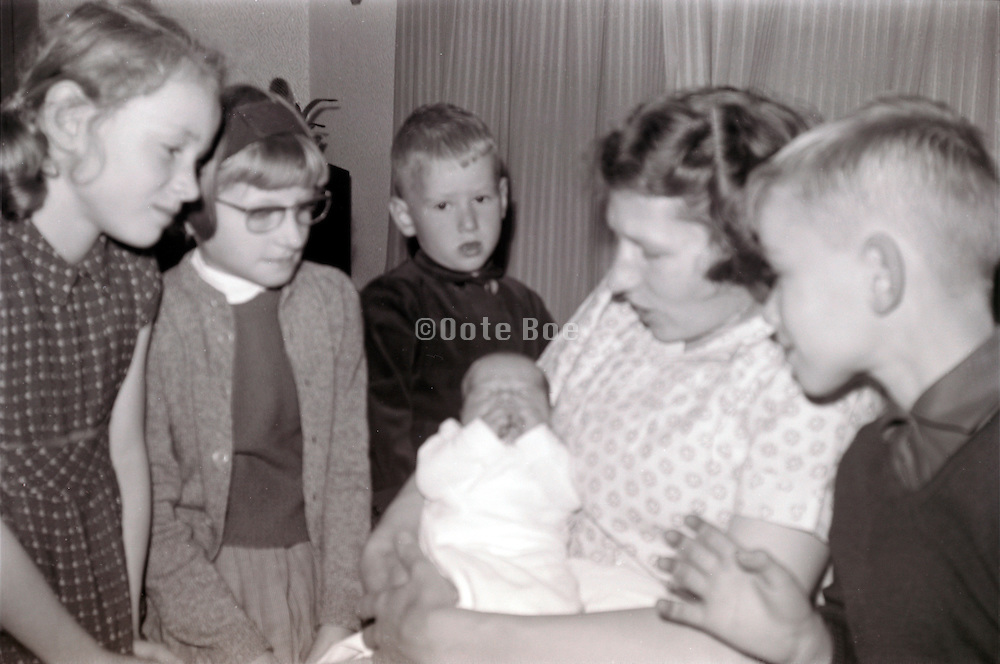 mother showing newborn baby to the family 1960s