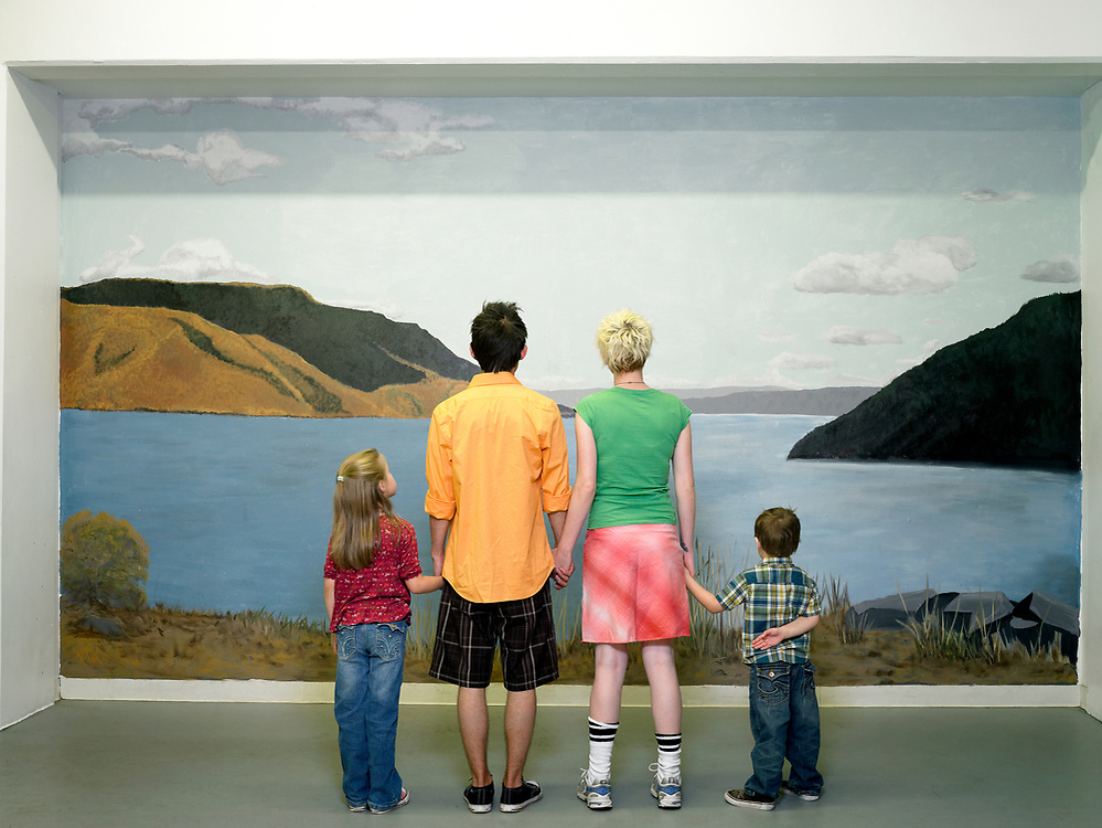 Family of four, mom, dad, daughter and son, looking at landscape mural, rear view