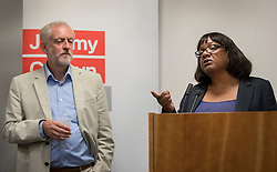 © Licensed to London News Pictures. 24/08/2016. London, UK. Labour party leader Jeremy Corbyn looks on as Diane Abbott answers journalists questions on NHS issues. Mr Corbyn faces increasing criticism after appearingng in a video sitting on the floor of a crowded train.  Virgin trains owner Sir Richard Branson released cctv footage appearing to show that seats were available. Photo credit: Peter Macdiarmid/LNP