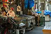 A woman working at the counter of a  a small fish shop in Tsukiji outer market Tokyo, Japan, Wednesday September 30th 2020