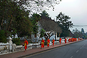 Each dawn Novice monks file around a temple circuit in Laos' old Royal Capital Luang Prabang, on the banks of the Mekong River, to collect alms from the town's residents and vistors. In the late 1800s, French colonial powers and the Lao aristocracy of Vientiane developed a new architectural fusion in Luang Prabang, inspired by local temples and materials, and French and Indochine architecture. The French brought in skilled Vietnamese builders to build two-storey villas throughout the town.