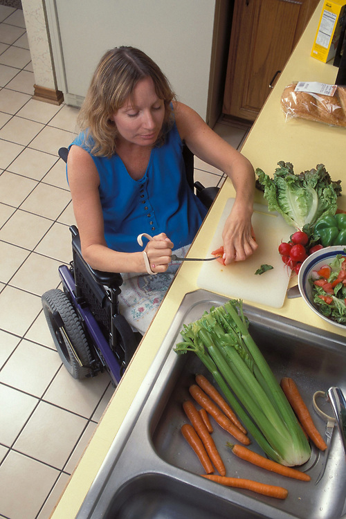 Forty (40) year old handicapped woman  makes salad in wheelchair accessable kitchen.  MR ©Bob Daemmrich /