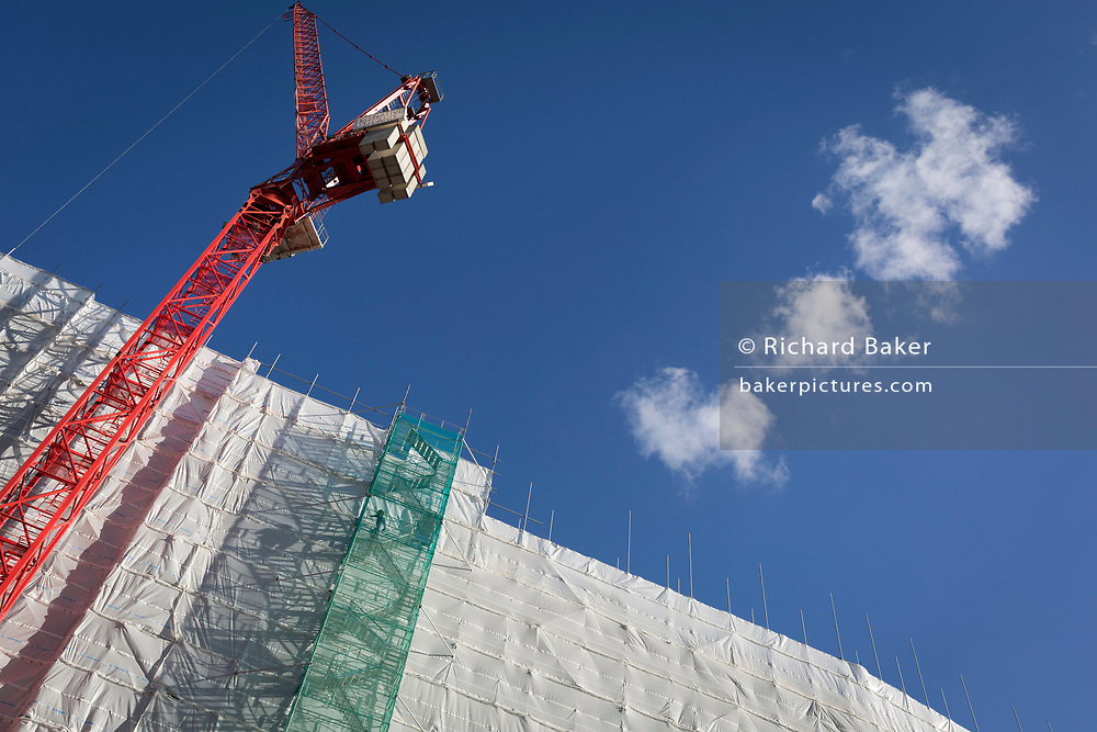 A construction worker reaches the very top of a tall gantry tower next to a crane tied to the side of an office building (formerly Express Newspapers) being renovated at the southern end of Blackfriars Bridge, on 27th October 2017, in London, England.
