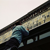 1. When was this photo taken?<br /> <br /> April, 2015<br /> <br /> 2. Where was this photo taken?<br /> <br /> Somerville Theater, Davis Square, MA<br /> <br /> 3. Who took this photo?<br /> <br /> Sofia Adams<br /> <br /> 4. What are we looking at here?<br /> <br /> One of the managers at the Somerville Theater is adjusting the movie titles on the marqui in Davis Square on a rainy day.<br /> <br /> 5. How does this old photo make you feel?<br /> <br /> This photo makes me deeply nostalgic for working here during the summer in college. It wasn't great pay, but we ate tons of free ice cream and popcorn and my coworkers were generally a delight.<br /> <br /> 6. Is this what you expected to see?<br /> <br /> I had no idea what was on this disposable camera. It had come with me over several moves and I had no idea when it had been shot.<br /> <br /> 7. What kind of memories does this photo bring back?<br /> <br /> This photo brings back memories of seeing the same movie credits over and over while cleaning theaters, of only eating popcorn and ice cream for a whole week (would not recommend,) of sneaking into the balcony to watch live performances, of drawing our own contributions to the Museum of Bad art, of cleaning up throw-up in the theater bathroom, of furiously biking to work to make it on time, of watching Keytar Bear play in Davis Square, of watching bad movies just to stay in the AC.<br /> <br /> 8. How do you think others will respond to this photo?<br /> <br /> I hope people can figure out what's going on.