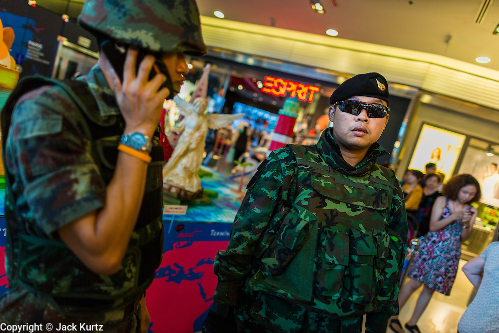 "01 JUNE 2014 - BANGKOK, THAILAND: Thai police and army patrol inside Terminal 21, a Bangkok shopping mall, after a flash mob protested against the coup in the mall. The Thai army seized power in a coup that unseated a democratically elected government on May 22. Since then there have been sporadic protests against the coup. The protests Sunday were the largest in several days and seemed to be spontaneous ""flash mobs"" that appeared at shopping centers in Bangkok and then broke up when soldiers arrived. Protest against the coup is illegal and the junta has threatened to arrest anyone who protests the coup. There was a massive security operation in Bangkok Sunday that shut down several shopping areas to prevent the protests but protestors went to malls that had no military presence.    PHOTO BY JACK KURTZ"