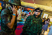 """01 JUNE 2014 - BANGKOK, THAILAND: Thai police and army patrol inside Terminal 21, a Bangkok shopping mall, after a flash mob protested against the coup in the mall. The Thai army seized power in a coup that unseated a democratically elected government on May 22. Since then there have been sporadic protests against the coup. The protests Sunday were the largest in several days and seemed to be spontaneous """"flash mobs"""" that appeared at shopping centers in Bangkok and then broke up when soldiers arrived. Protest against the coup is illegal and the junta has threatened to arrest anyone who protests the coup. There was a massive security operation in Bangkok Sunday that shut down several shopping areas to prevent the protests but protestors went to malls that had no military presence.    PHOTO BY JACK KURTZ"""
