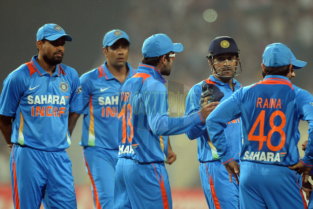 Mahendra Singh Dhoni captain of India  reacts as Virat Kohli of India exchange few words with Craig Kieswetter of England during the T20 International match between India and England held at the Eden Gardens Stadium, Kolkata on the 29th October 2011..Photo by Pal Pillai/BCCI/SPORTZPICS